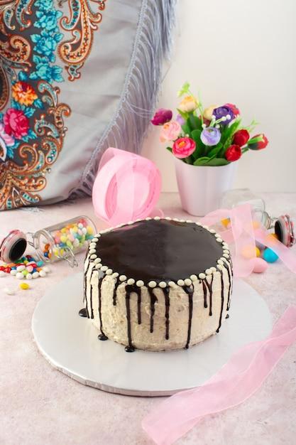 ピンクの机の上にキャンディーと正面のチョコレートケーキ 無料写真