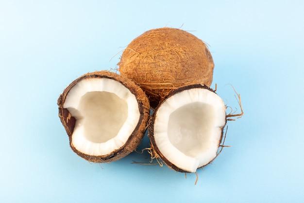スライスされた正面のココナッツとアイスブルーの背景熱帯のエキゾチックなフルーツナッツに分離された全体の乳白色の新鮮なまろやか 無料写真