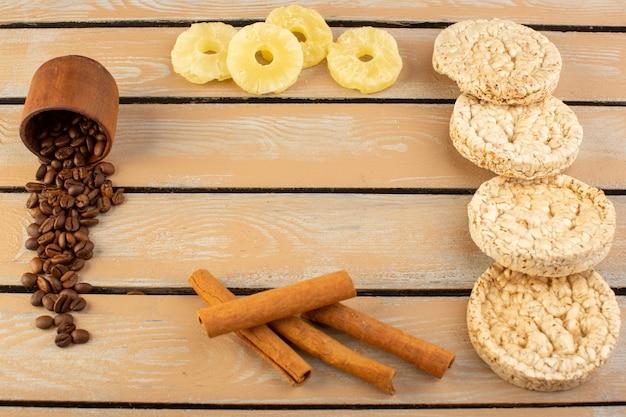 乾燥したパイナップルシナモンとクリームの素朴なデスクコーヒーシードドリンク写真穀物のクラッカーと正面のコーヒーシード 無料写真