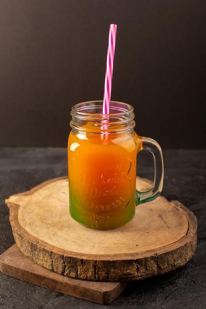 Вид спереди холодного коктейля, окрашенного внутри стеклянной банки с разноцветной соломкой, изолированной на деревянном столе, и темного цвета. Бесплатные Фотографии