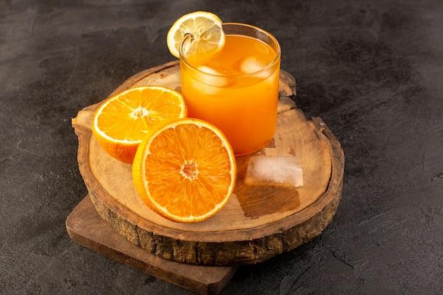 暗闇の中で分離されたアイスキューブオレンジとガラスの内側の色の正面の冷たいカクテル 無料写真