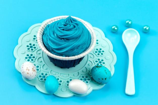 正面の色付きの卵と白、デザイン色の青に分離されたスプーン 無料写真