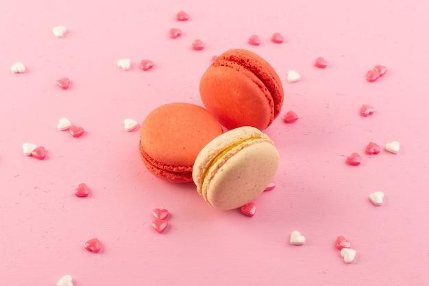 ピンクの机の上に丸みを帯びた形で美味しいフレンチマカロンの正面図 無料写真