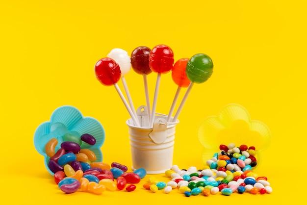 黄色の甘い砂糖色に分離されたロリポップと一緒に正面のカラフルなキャンディー 無料写真