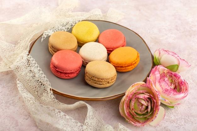 ピンクの机の上の皿の中にバラと正面のカラフルなフランスのマカロン 無料写真