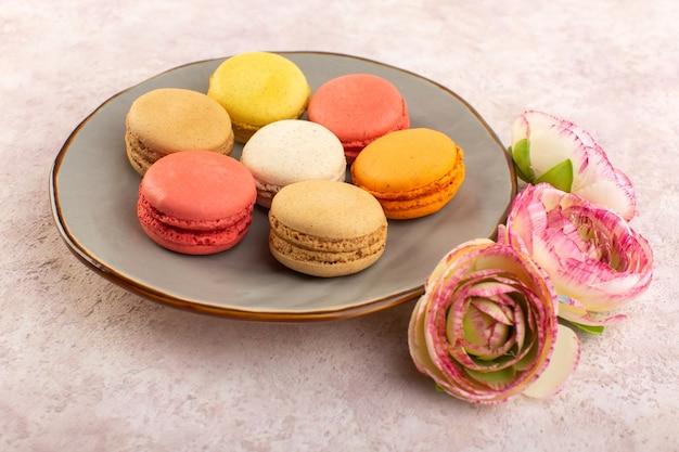 ピンクのデスクケーキビスケット色のバラと正面のカラフルなフランスのマカロン 無料写真