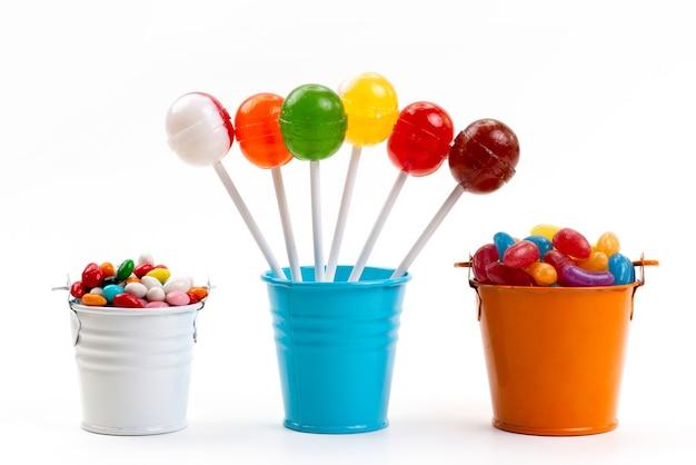 白、甘い砂糖色のバケツの中の色とりどりのキャンディーと一緒に正面のカラフルなロリポップ 無料写真