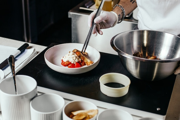 正面図のコックが白いスーツで食事を準備し、手袋を調理する 無料写真