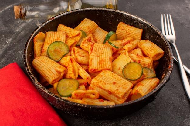 正面は、暗い表面に鍋にトマトソースとキュウリのイタリアンパスタを調理 無料写真