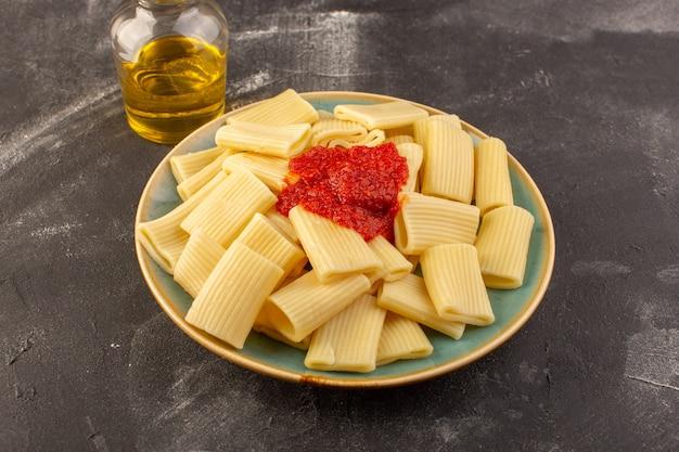 正面図は灰色の表面のプレート内のトマトソースとイタリアンパスタ 無料写真