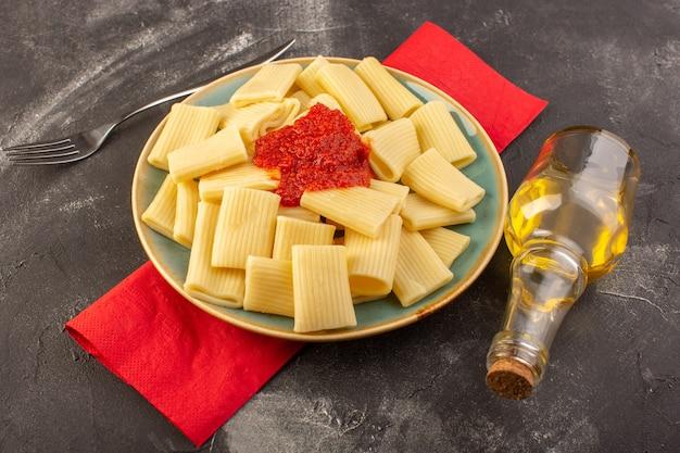 正面図は灰色のテーブルパスタイタリア料理の食事でプレート内のトマトソースとイタリアのパスタを調理 無料写真