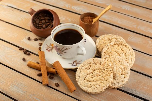 新鮮な茶色のコーヒーの種子とクリームの素朴なデスクのコーヒー種子ドリンク写真穀物のクラッカーとホットで強いコーヒーの正面図カップ 無料写真