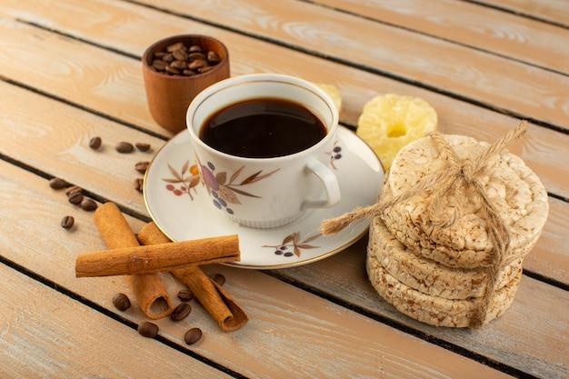新鮮で茶色のコーヒーシードシナモンとクリームの素朴なデスクコーヒーシードドリンク写真穀物のクラッカーとホットで強いコーヒーの正面図カップ 無料写真
