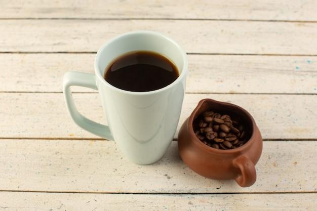 明るい表面のコーヒーカフェインに新鮮な茶色のコーヒーの種子と白いカップでコーヒーの正面図カップ 無料写真