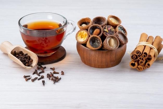 Чашка чая с рожками и корицей на белом, вид спереди, десерт чайный завтрак Бесплатные Фотографии