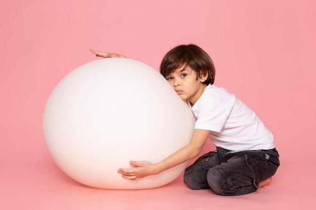 Вид спереди милый мальчик в белой футболке играет с белым мячом на розовом пространстве Бесплатные Фотографии