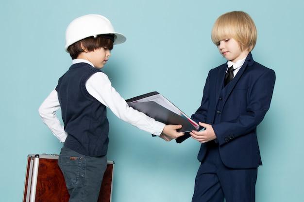 フォルダービジネス仕事ファッションを与える他の少年と一緒に茶色銀のスーツケースを持ってポーズをとって青いクラシックスーツの正面かわいいビジネスボーイ 無料写真
