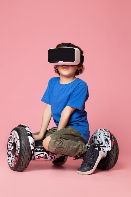 ピンクのスペースでセグウェイでvrを再生する青いtシャツで正面のかわいい子少年 無料写真
