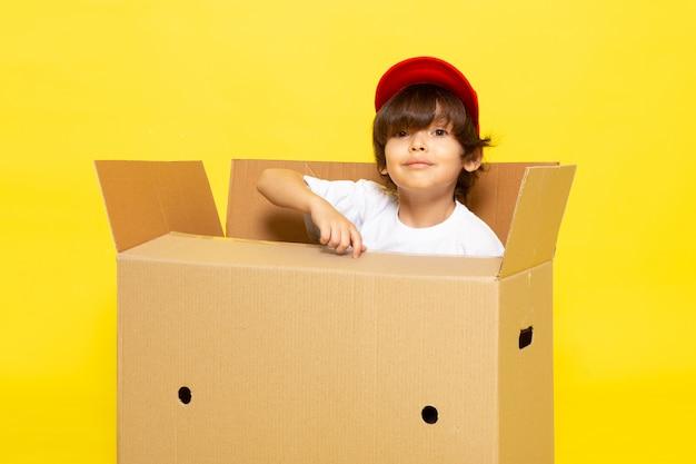 黄色の壁に茶色のボックスの中の白いtシャツの赤い帽子の正面のかわいい子供 無料写真