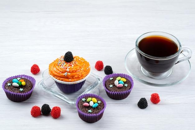 Вид спереди восхитительных пирожных внутри фиолетовых форм вместе с чашкой чая на белых конфетах конфетного цвета. Бесплатные Фотографии