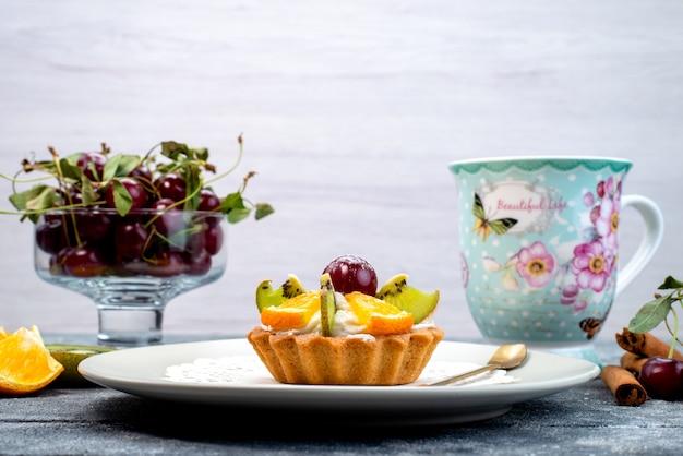 グレーとブルーのデスクのフルーツケーキビスケットにシナモンティーと一緒にクリームと新鮮なスライスフルーツが入った正面のおいしい小さなケーキ 無料写真