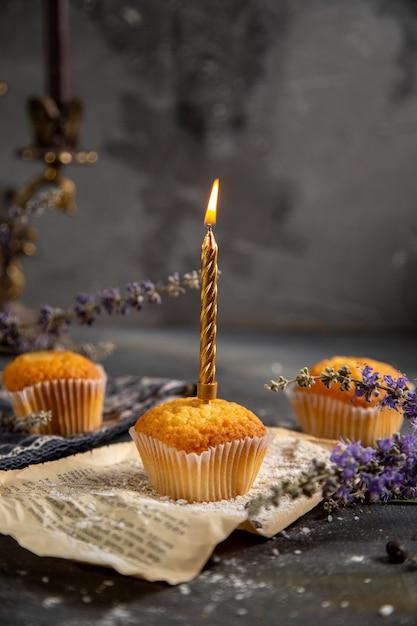 グレーのテーブルクッキーティービスケット甘い上にろうそくと紫色の花と正面のおいしい小さなケーキ 無料写真