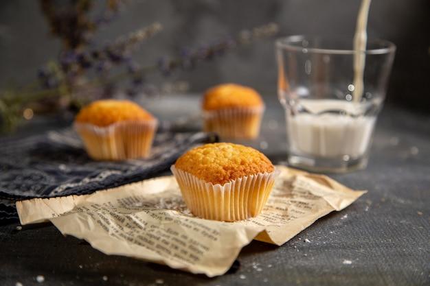 グレーのテーブルクッキーティービスケット甘い上に紫色の花と正面のおいしい小さなケーキ 無料写真