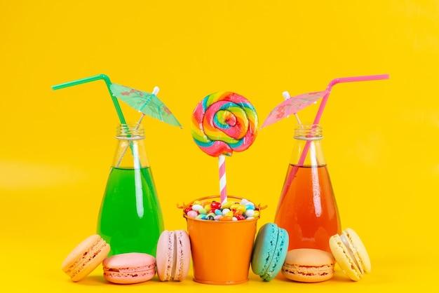 正面の飲み物と黄色のロリポップとキャンディーとともにカラフルでおいしいマカロン 無料写真