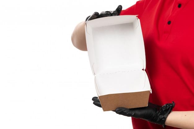 Вид спереди курьер женского пола в красной рубашке и черных перчатках, держа пустой пакет с едой Бесплатные Фотографии