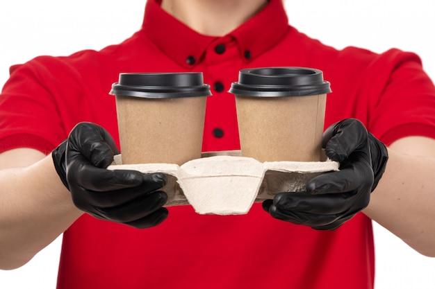 Вид спереди курьер женского пола в красной рубашке черные перчатки, держа кофейные чашки Бесплатные Фотографии
