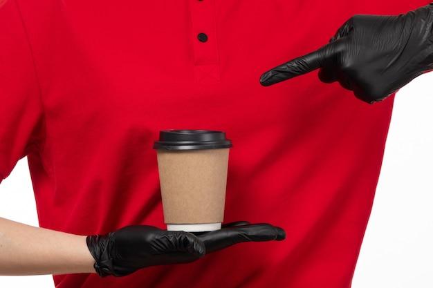 Вид спереди курьер женского пола в красной рубашке черные перчатки, держа кофе на белом Бесплатные Фотографии