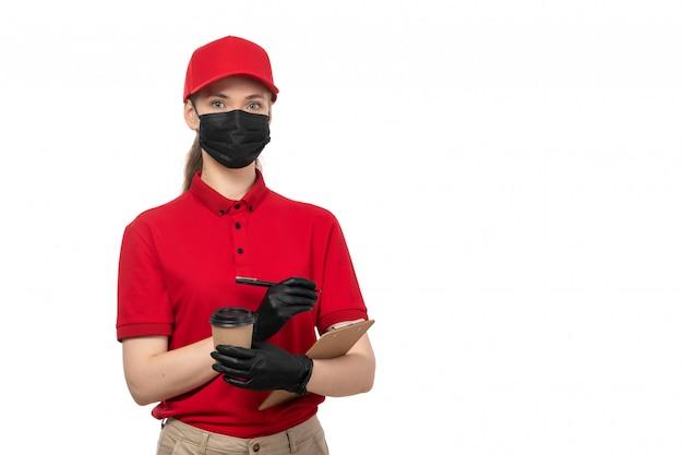 Вид спереди курьер женского пола в красной рубашке, красной шапочке, черных перчатках и черной маске, держа кофе и записывая Бесплатные Фотографии