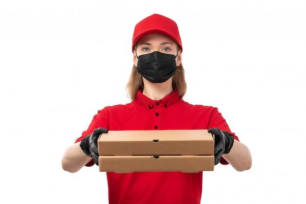 赤いシャツの赤い帽子の黒い手袋と白のピザの箱を保持している黒いマスクの正面図女性宅配便 無料写真