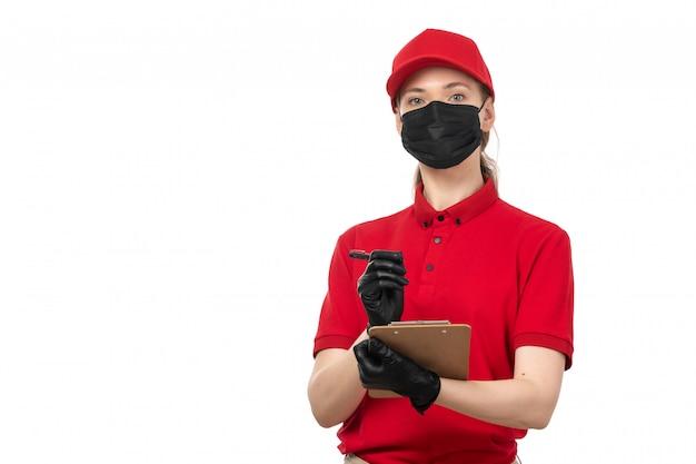 赤いシャツの赤い帽子の黒い手袋と白の注文を書き留める黒いマスクの正面女性宅配便 無料写真