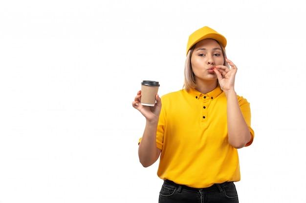 Вид спереди курьер женского пола в желтой кепке желтой рубашке и черных джинсах держит чашку кофе на белом фоне доставка пить девушка Бесплатные Фотографии