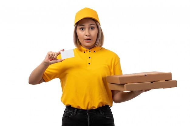 Вид спереди курьер женского пола в желтой рубашке, желтой кепке и черных джинсах, держащей коробки на белом фоне службы пиццы Бесплатные Фотографии