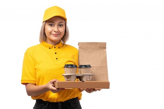 Вид спереди курьер женского пола в желтой рубашке желтой кепке и черных джинсах, держа кофе и пакеты с едой, улыбаясь на белом фоне службы доставки Бесплатные Фотографии