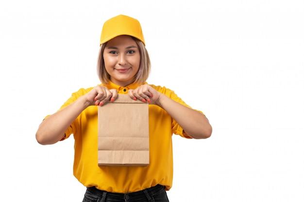 Вид спереди курьер женского пола в желтой рубашке желтой кепке и черных джинсах держит пакет еды и улыбается на белом Бесплатные Фотографии