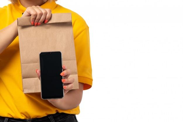 Вид спереди курьер женского пола в желтой рубашке желтой кепке черные джинсы, улыбаясь, держа смартфон и пакеты с едой на белом Бесплатные Фотографии