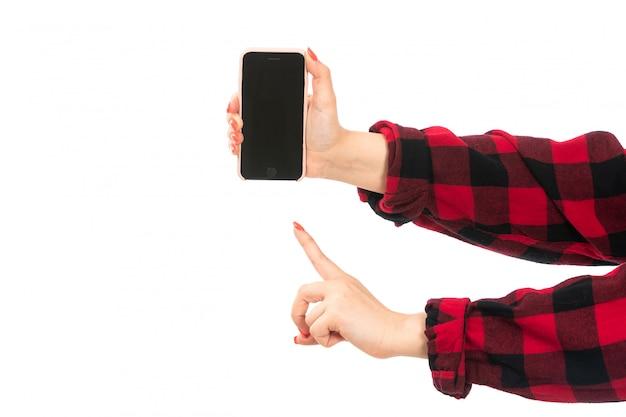 白の警告サインを示すスマートフォンを保持している黒赤の市松模様のシャツの正面の女性の手 無料写真