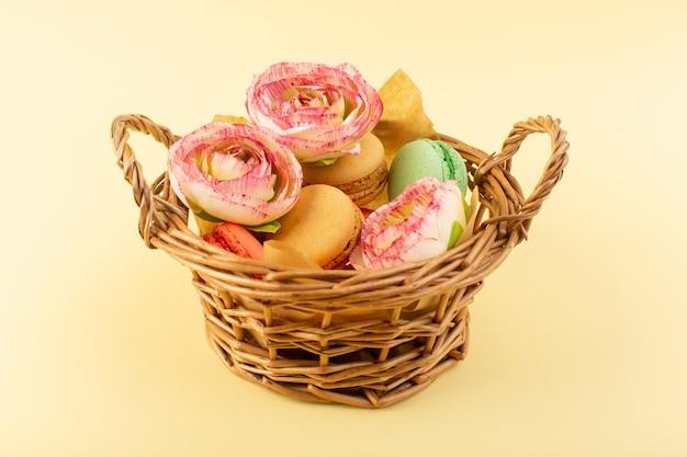 黄色のデスクビスケットケーキ砂糖甘いバスケットの内側の花と正面フレンチマカロン 無料写真