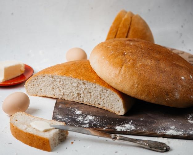 Вид спереди свежий хлеб круглый, сформированный с яйцами и цветком на белой поверхности, тесто для еды из булочки Бесплатные Фотографии