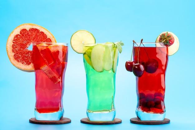 Вид спереди свежие фруктовые коктейли с кусочками свежих фруктов ледяное охлаждение на синем, напиток сок коктейль фруктовый цвет Бесплатные Фотографии