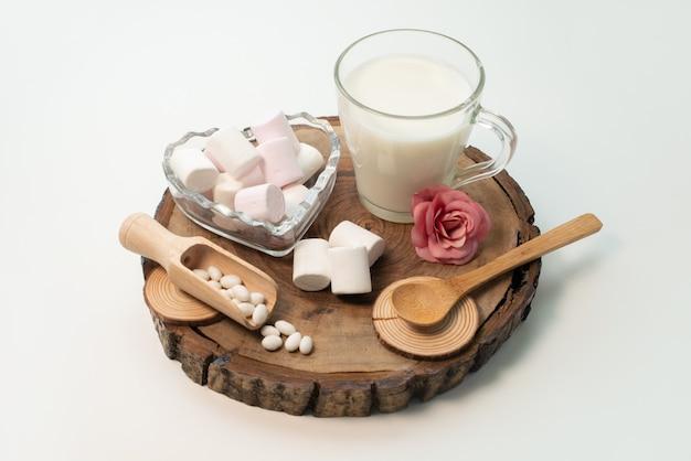 茶色の木製のキャンディー砂糖甘い茶色のマシュマロと一緒に正面の新鮮な牛乳 無料写真