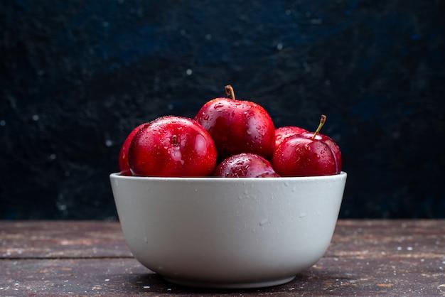 Вид спереди свежие красные сливы, спелые и спелые внутри белой тарелки на деревянном столе, фруктовый сок из мякоти Бесплатные Фотографии