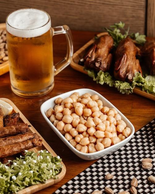 Вид спереди жареное мясо с пивом и орехами на коричневом деревянном столе. Бесплатные Фотографии