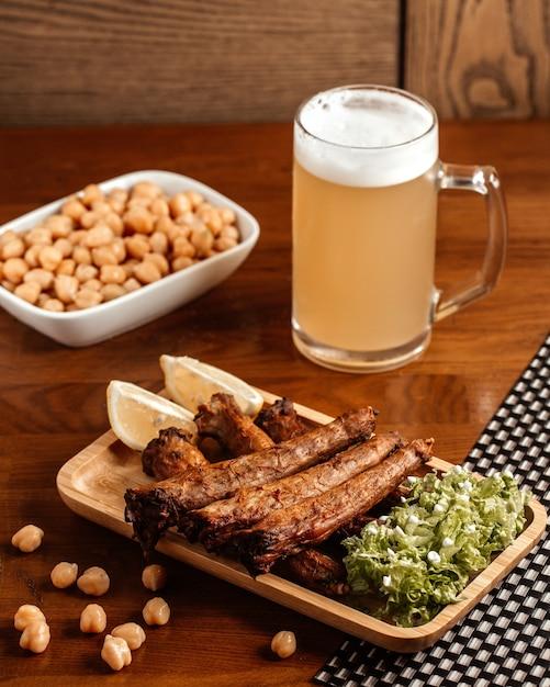 Вид спереди жареное мясо с пивом, лимоном и фасолью на коричневом деревянном столе. Бесплатные Фотографии