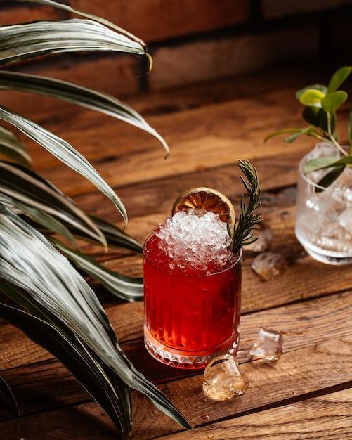 Фруктовый коктейль с кубиками льда на коричневом деревянном столе, вид спереди, коктейльный сок Бесплатные Фотографии