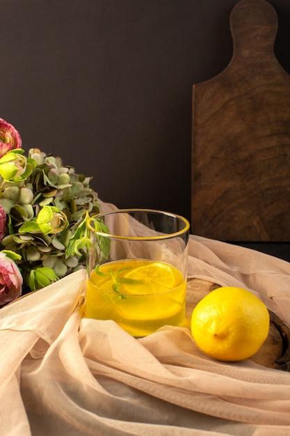 全体のレモンと茶色の木製の机の上の花と灰色の背景のカクテルレモンドリンクに沿って透明なガラスの中にジュースレモンジュースが入った正面図のガラス 無料写真
