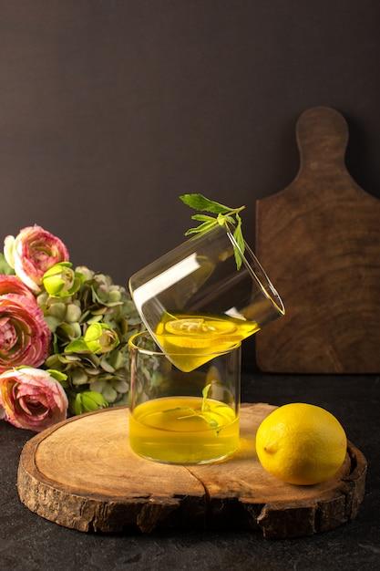 Очки спереди с соком лимонного сока внутри прозрачных стаканов вдоль целого лимона и цветов на коричневом деревянном столе и сером фоне коктейльного лимонного напитка Бесплатные Фотографии